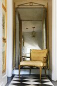 Upholstered chair in front of mirror with gold frame on checkered floor in transition