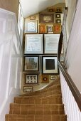View from below of a traditional staircase with carpet and framed pictures on the wall