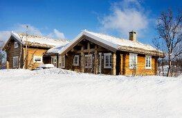 Wooden houses in snowy landscape below blue sky