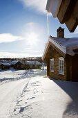 Holzhaussiedlung in verschneiter Winterlandschaft