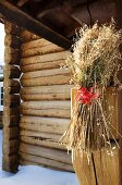 Sheaf of cereal tied to wooden structure with red ribbon in front of outer wall of log cabin