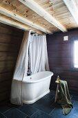 Vintage bathtub with shower curtain in corner of bathroom with grey tiled floor in rustic, modern interior