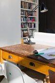 weiße Panton Chairs vor alter Schulbank mit aufgeschlagenem Malbuch und alter Schreibtischlampe