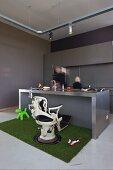 Alter Behandlungsstuhl vor der Theke einer minimalistischen Designerküche