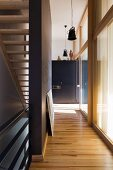 Gangflucht zwischen Glasfassade und schmaler Wohnraumtreppe mit alten, restaurierten Hängelampen im Industriestil