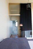 Blick über das Doppelbett in das Bad Ensuite hinter dunklem Vorhang
