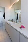 Minimalistischer Waschtisch vor großem Wandspiegel im weissen Bad
