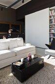 Sonniger Wohnraum mit schwarz lackierter Überseekiste als Couchtisch vor weißem Sofa