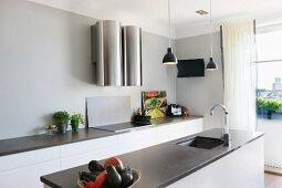Freistehender Küchenblock mit eingebauter Spüle unter Hängeleuchten und Küchenzeile an Wand mit futuristischem Dunstabzug
