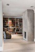 Minimalistischer Wohnraum mit offenem Kamin in betonierter Wand gegenüber Sessel vor Einbaubücherregal