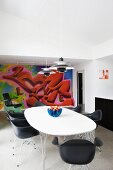 Classic, black shell chairs and table with white top in front of graffito mural on wall of modern interior
