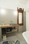 Modern washstand next to wall-mounted mirror with antique wooden frame in designer bathroom