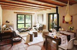 Essplatz mit Bauhausstühlen und Sitzhocker vor Loungebereich in offenem Wohnraum mit Holzdecke