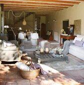 Loungebereich mit mobilem Bodentisch auf Teppich und Sofas in verschiedenen Stilen vor Essbereich in schlichtem, offenem Wohnzimmer