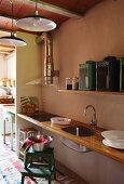 Schlichte Küchenzeile mit Holz Arbeitsplatte und Spüle in Wandnische eingespannt unter Regal mit Vintage Laternen in offenem Wohnraum mit Retroflair