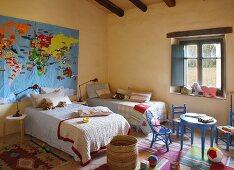 Gelbgetöntes Schlafzimmer mit Einzelbetten und blaue Kinderstühle um Tisch vor dem Fenster