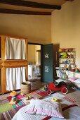 Gelb getöntes Schlafzimmer mit Spielzeugen und Kinderfahrzeug vor offener Tür