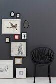 Schwarze, geflechtartiger Kunststoffstuhl vor schwarzer Wand mit Bildern und Tiermotiven