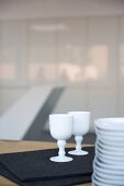Porcelain goblets on black felt mat next to stacked plates on table