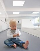 Toddler sitting on floor next to white futuristic bench in contemporary interior