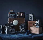 Collection of antique cameras and leather cases on table with tablecloth against black background