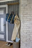 Bag and laundry bag hanging from coat rack in hallway with grey wood panelling