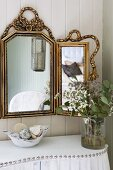 Glass vase of flowers on curved console table with white cover and decorative studs below gilt-framed, triple mirror on wooden wall