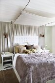 Grey bedspread on double bed with quilted headboard against pale grey curtain on wall and below light canopy mounted on ceiling