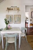 Retro dining area in kitchen-dining room with classic Scandinavian chairs and framed botanical drawings on wall