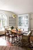 Dining table, classic upholstered chairs and wicker armchairs; woven rug and country-house-style, glass-fronted dresser