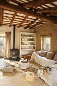 Comfortable couch behind stacked pouffes in rustic living room with wood-burning stove below wood-beamed ceiling