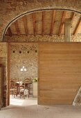 Wooden partition in hall-like interior of converted, Mediterranean country house; view of dining area in background