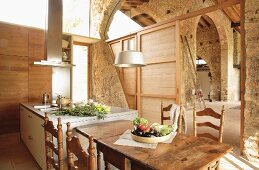 Modern kitchen island and dining area with turned, Spanish wooden chairs in spacious, restored stone house