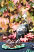 Chocolate pastries & autumnal arrangement of oil lamps & autumn fruits on garden table