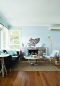 60's living room with wooden coffee table on a sisal rug and black couch in front of a fireplace in a bright blue room