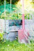 Spaten lehnt am Hochbeet mit Erdbeeren im Garten
