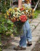 Woman carrying summer bouquet of dahlias, alstroemeria and rudbeckia