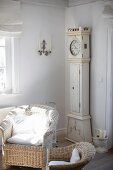 Wicker chair with white cushions and nostalgic grandfather clock in living room