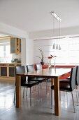 Designer-Essplatz in offenem Wohnraum mit Blick durch breiten Durchgang auf Küchenzeile