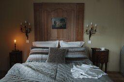 Eclectic bedroom with bedspread in modern tones of grey on double bed combined with wood panelling flanked by antique sconce lamps and Rococo bedside cabinets
