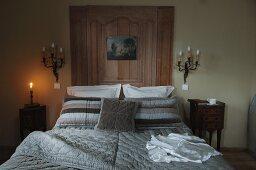Doppelbett mit Bezug in modernen Grautönen im Stilmix kombiniert mit einer von antiken Wandleuchtern flankierten Wandvertäfelung und Rokoko Kommode