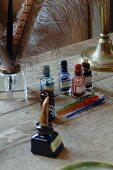 Fläschchen mit verschiedenfarbigen Tinten und Federkiele auf altem Schreibtisch