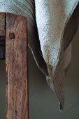Handtuch im edlen Naturlook neben dem Holzrahmen einer Stuhllehne