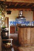 Rustikale Küche mit antiken, blauen Wandfliesen und einfachen Holzfronten zu Terrakottafliesen im Vintage-Look