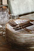 Stack of romantic floral plates and cutlery; old wine glasses in background
