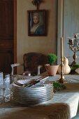 Stapel antiker Blümchenteller und Kerzenständer auf Esstisch