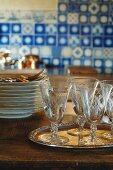 Geätzte, alte Weingläser auf Silbertablett vor Tellerstapel; antike Fliesen in Delfter Blau unscharf im Hintergrund