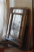 Antique, carved wooden picture frame and leather-bound tome with gold embossing leaning on wall