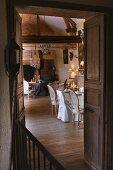 Blick durch offene Flügeltür auf Essplatz und Sitzecke vor Kamin in traditionellem Wohnraum