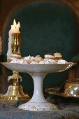 Pralinen Konfekt auf Porzellanschale mit Fuss vor Messing-Kerzenständer und brennender Kerze